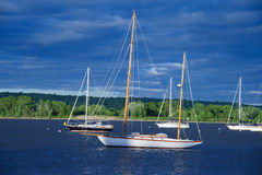 Yachts at Sunset. Moored yachts bask in setting sun's rays under cloudy sky Stock Photo
