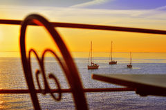 Yachts at sunset, view from terrace Royalty Free Stock Images