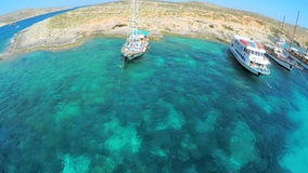Yachts with tourists stand near a picturesque sea shore. Aerial view. Malta stock footage
