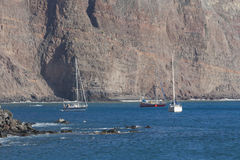 Yachts under rocks of La Gomera Stock Photo