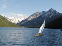 Yachts with white sail on the lake in the mountains stock photos