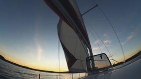 Yachtsegeln im offenen Wasser Segel bewegt in Wind, Boot durchläuft Wasser wellenartig Schöne Wasserlandschaft auf Sonnenuntergan stock video