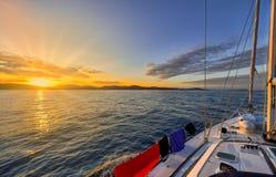 Yachtsegling in mot solnedgången Arkivfoto