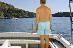 Yachtsman. Man looking at the seacoast standing on a yacht stern Stock Images