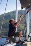 Yachtsman pulls the rope on the mast, on his sailing yaht boat Stock Photo