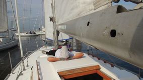 Yachtsman sleeping on deck of sailing yacht. Vacation, holiday. Stock footage stock video