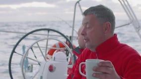 Yachtsman stojaki na pokładzie żeglowania trzyma filiżankę herbata podczas zmierzchu zdjęcie wideo