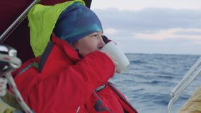 Yachtsman stojaki na pokładzie żeglowania trzyma filiżankę herbata podczas zmierzchu zbiory