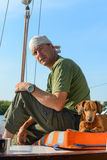 Yachtsman travels with his dog on an old sailboat. Stock Photography