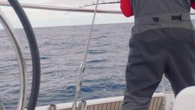Yachtsman trolls fish standing on board of yacht. Fish trolling from board of yacht sailing in ocean stock video footage