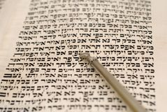 Yad and torah. A silver yad pointer on a page from the torah, the first five books of the hebrew bible.  selective focus, shallow depth of field Royalty Free Stock Photo