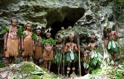 Yaffi för några personer stam i krigmålarfärg med pilbågar och pilar i en grotta runt om en rituell brand New Guinea ö, Royaltyfri Foto