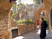 Yaffo, Israel Der orthodoxe Priester überprüft ncient Strukturen auf der Straße lizenzfreie stockfotografie