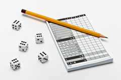 Yahtzee. Five dice, a yahtzee notepad and a pencil lying on white background Royalty Free Stock Photos