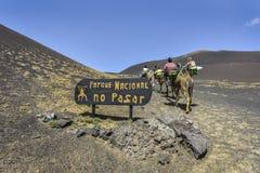 YAIZA, LANZAROTE/ESPANHA - 12 DE ABRIL DE 2017: Turistas no camelo que incorpora o sinal 'parque nacional do parque nacional de T fotografia de stock