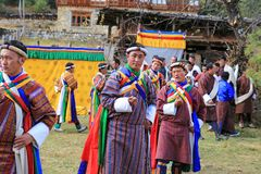 Yak Festival Participants Dance and Sing in Bhutan. Colorful male participants sing and dance in local Yak Festival in rural Bhutan Royalty Free Stock Image