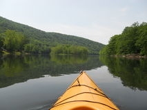'Yak on. Looking out of the tip of a yellow kayak down the tree-reflecting Allegheny River stock photos