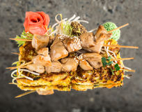 Yakitori chicken skewers. On vegetable omelette over concrete background Stock Photography