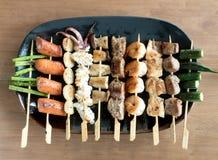 Yakitori: Japanese bite-sized food skewers: asparagus, sausage, scallop, squid, mushroom, prawns, chicken, pork, beef and okra. A platter of Yakitori: Japanese Stock Photos