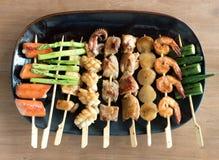 Yakitori: Japanese bite-sized food skewers: asparagus, sausage, scallop, squid, mushroom, prawns, chicken, pork, beef and okra. A platter of Yakitori: Japanese Stock Image