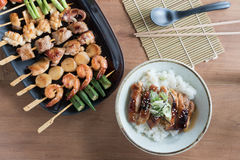 Yakitori: Japanese grilled bite-sized food on skewers and chicken teriyaki rice bowl. Top view of Yakitori: Japanese grilled bite-sized food on skewers and stock images