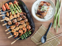 Yakitori: Japanese grilled bite-sized food on skewers and chicken teriyaki rice bowl. Top view of Yakitori: Japanese grilled bite-sized food on skewers and stock photos