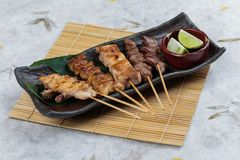 Yakitori Japanese-Style Grilled Chicken Skewers with chicken and internal organ served with sliced lime on black stone plate. Yakitori Japanese-Style Grilled Royalty Free Stock Photo