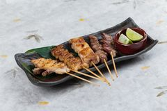 Yakitori Japanese-Style Grilled Chicken Skewers with chicken and internal organ served with sliced lime on black stone. Stock Image