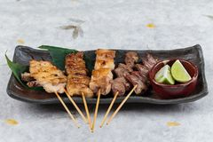 Yakitori Japanese-Style Grilled Chicken Skewers with chicken and internal organ served with sliced lime on black stone. Stock Photo