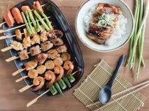 Yakitori: O japonês grelhou o alimento tamanho de mordidas em espetos e em bacia de arroz do teriyaki da galinha Fotos de Stock