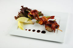 Yakitori with shrimps, bacon and avocado. On white plate Royalty Free Stock Photography