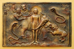 The Yaksa Sulapani tries to harass Bhagavan Mahavira while absorbed in deep meditation. Street bas relief on the wall of Jain Temple also called Parshwanath Royalty Free Stock Image
