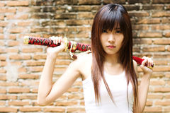 Yakuza girl. Thai sexy girl holding the japanese sword Royalty Free Stock Photo