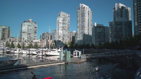 Yaletown, Vancouver Rowers 4K. UHD. Sunrise reflects off Yaletown condominiums as rowers pass by. Vancouver. British Columbia, Canada. 4K. UHD stock footage