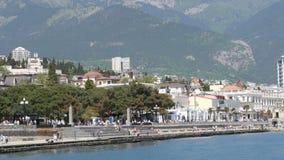 Yalta, Crimée - 1er mai 2018 : Remblai de la ville de mer, sur laquelle les gens marchent Une ville de mer en montagnes banque de vidéos