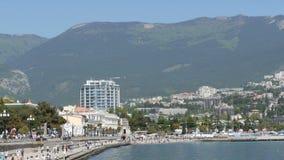 Yalta, Crimea - 1 de mayo de 2018: Terraplén de la ciudad del mar, en la cual la gente camina Una ciudad del mar en montañas metrajes