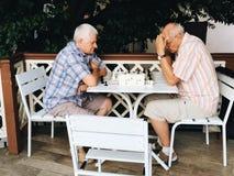 Two elderly men playing chess on street. Yalta, Crimea - September 21, 2017: two elderly men playing chess on street royalty free stock photography