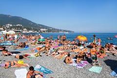 Yalta, de Oekraïne - September 15, 2012: De mensen rusten op overzees kiezelsteenstrand met blauw water Mening van onderstel Stock Fotografie