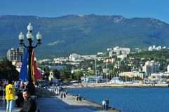 Yalta, Ukraine, View on a promenade along seaside. Yalta, Ukraine, May 2011. View on a promenade along seaside and Yalta city and mountains in the background royalty free stock photo