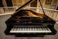 Yamaha Grand Piano. A `Yamaha` brand, black grand piano in the middle of a music hall, `Sala del Minor Consiglio` in Palazzo Ducale, Genoa, Italy royalty free stock images