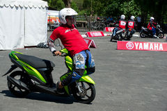 Yamaha scooter stunt drivers. Sporting event in Bali, Indonesia organised by Yamaha for presentation of a new scooter model with stunt riding competition of Royalty Free Stock Photography