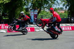 Yamaha scooter stunt drivers. Sporting event in Bali, Indonesia organised by Yamaha for presentation of a new scooter model with stunt riding competition of Royalty Free Stock Image