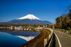 Yamanaka lake and village with mount Fujisan. Yamanaka lake shore and village with mount Fujisan and skyline reflection on water against blue sky. Here is 1 of 5 Royalty Free Stock Photography