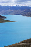 Yamdrok Lake. Is one of the three largest sacred lakes in Tibet. It is over 72 km long. The lake is surrounded by many snow-capped mountains and is fed by Stock Photos