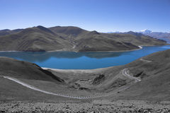 Yamdrok lake in Tibet. Yamdrok lake surrounding by snow mountains which is the most sacred lake in Tibet stock image