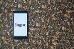 Yandex-Logo auf Smartphone auf Hintergrund von kleinen Steinen Lizenzfreie Stockfotos