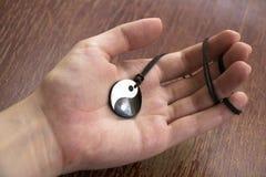 Yang för yin för handinnehavpärla halsband på träbakgrund royaltyfri foto