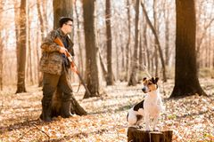 Yang hunter with a dog on the forest stock image