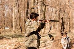 Yang jägare med en hund på skogen som jägaren siktar royaltyfri fotografi