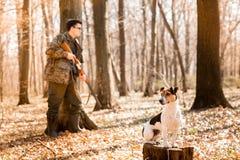 Yang j?gare med en hund p? skogen fotografering för bildbyråer